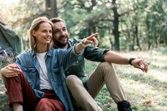 Pareja casada alegre que abraza mientras que se relaja en bosque Fotografía de archivo libre de regalías