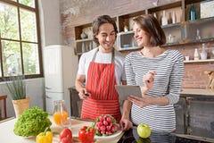Pareja casada alegre que prepara la comida sana Imagenes de archivo