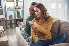 Pareja casada alegre que usa los teléfonos móviles para el entretenimiento fotografía de archivo