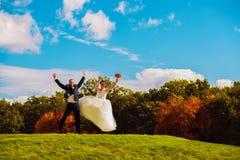 Pareja casada de salto feliz en campo Foto de archivo libre de regalías