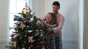 Pareja casada feliz que adorna el árbol de navidad almacen de video
