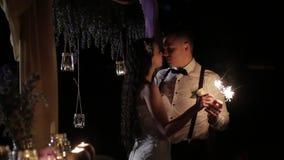 Pareja casada feliz que quema las luces de Bengala al aire libre El novio y la novia sonrientes miran a los ojos con el amor, cie almacen de video
