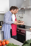 Pareja casada fresca joven en la cocina que cocina junto frita Imagen de archivo libre de regalías