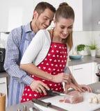 Pareja casada fresca joven en la cocina que cocina junto la carne asada Imagen de archivo