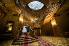 Pareja casada hermosa que lleva a cabo las manos que vienen abajo las escaleras en el interior de madera rico Fotos de archivo libres de regalías