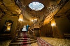 Pareja casada hermosa que lleva a cabo las manos que vienen abajo las escaleras en el interior de madera rico Fotografía de archivo libre de regalías