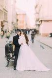 Pareja casada hermosa que se coloca de abarcamiento en la ciudad vieja con arquitectura maravillosa Foto de archivo libre de regalías