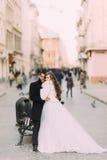 Pareja casada hermosa que se coloca de abarcamiento en la ciudad vieja con arquitectura maravillosa Imagen de archivo libre de regalías