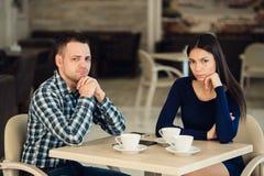 Pareja casada infeliz joven que tiene pelea seria en el café imagenes de archivo