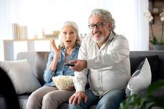 Pareja casada madura alegre que ve la TV junto Fotos de archivo libres de regalías