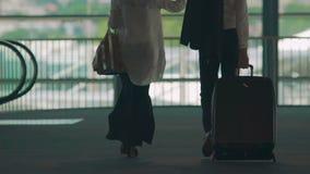 Pareja casada que camina a través del paso superior del aeropuerto, maleta que lleva del hombre, días de fiesta almacen de video
