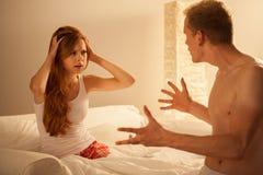 Pareja casada que discute en cama Fotos de archivo