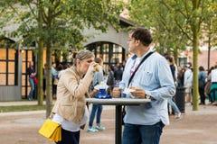 Pareja casada que espera a un bebé y que come la comida de la calle en el parque imagen de archivo