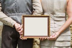Pareja casada que lleva a cabo la publicidad o tablero de mensajes en manos Fotografía de archivo libre de regalías