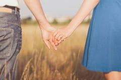 Pareja casada que lleva a cabo las manos en la puesta del sol Imagenes de archivo