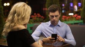 Pareja casada que no presta ninguna atención que enrolla el uno al otro las páginas en smartphones metrajes