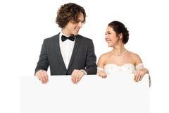 Pareja casada que presenta con un tablero en blanco del anuncio fotos de archivo