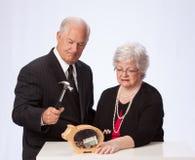 Pareja casada que rompe el Piggybank para el retiro Imagen de archivo
