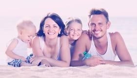 Pareja con dos niños que mienten en la playa Fotografía de archivo
