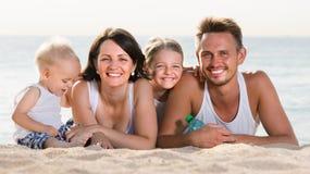 Pareja con dos niños que mienten en la playa Foto de archivo libre de regalías