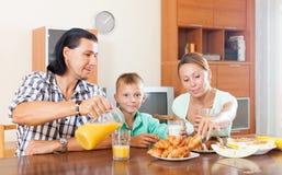 Pareja con el hijo que desayuna con los cruasanes en mañana Fotografía de archivo