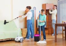 Pareja con el hijo que limpia con la aspiradora junto Imagen de archivo