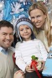 Pareja con el hijo que se sostiene presente en Front Of Christmas Tree Foto de archivo