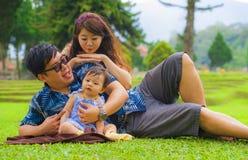 Pareja coreana asiática cariñosa feliz joven de los padres que goza junto del bebé dulce de la hija que asiste en hierba en el pa imágenes de archivo libres de regalías
