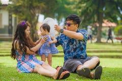 Pareja coreana asiática cariñosa feliz joven de los padres que goza junto del bebé dulce de la hija que asiste en hierba en el pa fotos de archivo