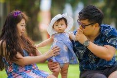 Pareja coreana asiática cariñosa feliz joven de los padres que goza junto del bebé dulce de la hija que asiste en hierba en el pa imagenes de archivo