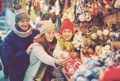 Pareja de la familia con la hija adolescente que elige la decoración de la Navidad Foto de archivo libre de regalías