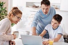 Pareja de la familia que cuida que ayuda a su hijo con la preparación Imágenes de archivo libres de regalías