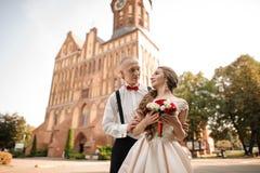 Pareja de matrimonios feliz con un ramo que se casa que se coloca en fondo del edificio hermoso imágenes de archivo libres de regalías