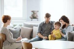 Pareja de matrimonios joven con el hijo durante terapia de familia con el consejero imagenes de archivo