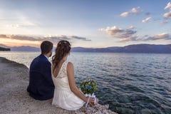 Pareja de matrimonios joven en una 'promenade' de la costa fotos de archivo
