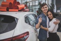 Pareja de matrimonios joven preciosa que compra el nuevo coche junto imagenes de archivo