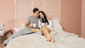 Pareja de matrimonios joven que come el desayuno en su cama en la cámara lenta metrajes