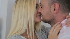 Pareja de matrimonios que se besa cerca de luces de hadas en casa almacen de metraje de vídeo