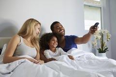 Pareja e hija de la raza mixta que ven la TV en cama junto Imagenes de archivo