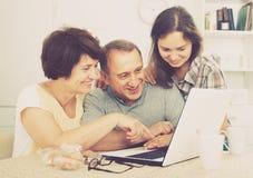 Pareja e hija mayores con el ordenador portátil en casa Fotos de archivo
