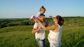 Pareja embarazada con la hija del niño que camina en los campos verdes que tienen tiempo libre almacen de metraje de vídeo
