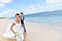 Pareja feliz casada que corre en la playa arenosa Imagen de archivo