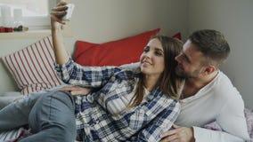 Pareja feliz casada que toma el portrain del selfie mientras que miente en cama en casa por la mañana foto de archivo