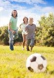 Pareja feliz con el hijo que juega con el balón de fútbol Imagen de archivo libre de regalías