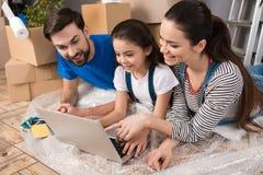 Pareja feliz con la pequeña hija que miente en el plástico de burbujas, mirando la pantalla del ordenador portátil en la reparaci foto de archivo