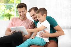 Pareja gay masculina con el hijo adoptivo que descansa en casa Fotos de archivo