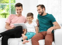 Pareja gay masculina con el hijo adoptivo que descansa en casa Imágenes de archivo libres de regalías