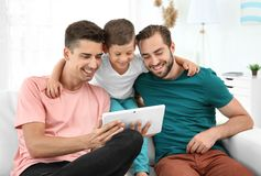 Pareja gay masculina con el hijo adoptivo que descansa en casa Imagenes de archivo