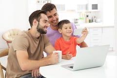 Pareja gay masculina con el hijo adoptivo que pasa el tiempo junto Imagen de archivo libre de regalías