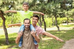 Pareja gay masculina con el hijo adoptivo que se divierte en parque Fotos de archivo